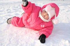 Die frohen Kindlagen auf einem Schnee Lizenzfreie Stockfotografie