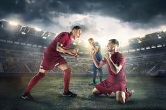 Die Fußballspieler in der Bewegung auf dem Feld des Stadions Lizenzfreies Stockfoto