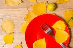 Die Gabel liegt auf einer roten Platte auf einer Tabelle, die mit gelbem leav bedeckt wird Stockfoto