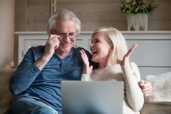 Die Gatten, die auf Couch sitzen, glaubt glücklichen empfangenen guten Nachrichten online stockfotografie