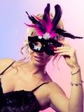 Die gealterte Frauenmitte hält Karnevalsmaske Stockfotografie