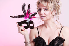 Die gealterte Frauenmitte hält Karnevalsmaske Stockbild