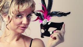 Die gealterte Frauenmitte hält Karnevalsmaske Stockfotos