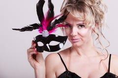 Die gealterte Frauenmitte hält Karnevalsmaske Stockbilder