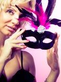 Die gealterte Frauenmitte hält Karnevalsmaske Lizenzfreies Stockbild