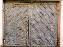 Die gealterten Tore der alten Garage Graue Farbe und wenig Tür Lizenzfreies Stockbild