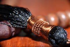 Die Gebetsperlen werden vom Holz im Braun mit einem Bündel des schwarzen Fadens gebunden gemacht lizenzfreie stockfotos