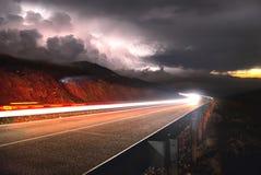 Die Gebirgsstraße mit dem Auto, das durch den Sonnenuntergang auf dem Recht und ein Gewitter mit dem gelassenen Blitz überschreit Stockfotografie