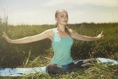 Die geeignete blonde junge Frau, die auf der Natur mit Augen meditiert, schloss Stockbilder