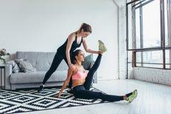Die geeignete Frau, die das Ausdehnen tut, trainiert mithilfe des Freunds, der zu Hause ihr Bein hält stockbilder