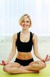 Die geeignete Frau der Junge, die auf der Yogamatte sitzt und meditiert lizenzfreie stockfotografie