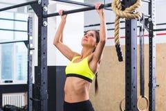 Die geeignete Frau des Athleten, die Zug durchführt, ups in eine Stange, die an der Turnhalle trainiert lizenzfreie stockbilder