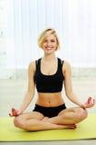 Die geeignete Frau, die auf der Yogamatte sitzt und meditiert stockbilder