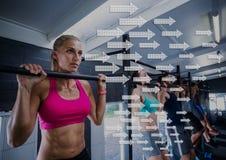 Die geeignete Frauenausführung ziehen Übung in der Turnhalle gegen Richtungspfeile im Hintergrund hoch Lizenzfreies Stockfoto