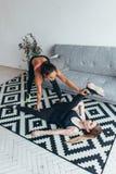 Die geeignete junge Frau, die das Ausdehnen tut, trainiert mithilfe des persönlichen Trainers zu Hause stockbild