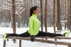 Die geeignete Sportlerin, die das aufgeteilte Ausdehnen des linken Beines tut, trainiert draußen im Holz Vorbildlicher trainieren Lizenzfreie Stockbilder