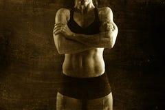 Die geeignete und starke Sportfrau, welche die Aufstellung aufsässig in der kühlen Haltung mit Borte hält, errichtete Körper Stockfotos