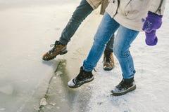 Die Gefahr des Fußes versuchen, das dünne Eis nahe dem Ufer prüfend Ein Paar Liebhaber gehen mit einem Weg entlang einem gefroren stockfoto