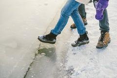 Die Gefahr des Fußes versuchen, das dünne Eis nahe dem Ufer prüfend Ein Paar Liebhaber gehen mit einem Weg entlang einem gefroren lizenzfreie stockbilder