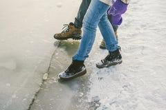 Die Gefahr des Fußes versuchen, das dünne Eis nahe dem Ufer prüfend Ein Paar Liebhaber gehen mit einem Weg entlang einem gefroren stockbild
