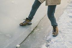 Die Gefahr des Fußes versuchen, das dünne Eis nahe dem Ufer prüfend Ein Paar Liebhaber gehen mit einem Weg entlang einem gefroren lizenzfreies stockbild