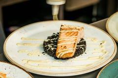 Die gegrillten Lachse, die auf eine Platte mit schwarzem Bulgur gesetzt werden, kochen Bedeckung mit dem Kleiden stockbild
