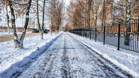Die geklärte Straße im Park, gesäubert in Winter in der Stadt, die Straße säuberte bis zum einem sonnigen Tag Asphalt im Schnee a Stockfoto