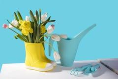 Die gelben Gummistiefel mit einem Blumenstrauß von Blumen von gelben Narzissen und von weißen und rosa Tulpen auf weißem Holztisc stockfotografie