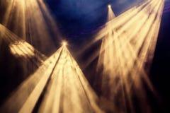 Die gelben hellen Strahlen vom Scheinwerfer durch den Rauch am Theater oder am Konzertsaal Lichttechnische Ausrüstung für eine Le stockfotografie