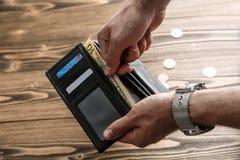 Die Geldbörse des schwarzen Mannes in den Mannhänden Stockfoto