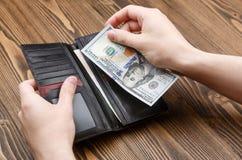 Die Geldbörse des schwarzen Mannes in den Mannhänden Lizenzfreie Stockfotos