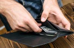 Die Geldbörse des schwarzen Mannes in den Mannhänden Lizenzfreie Stockbilder