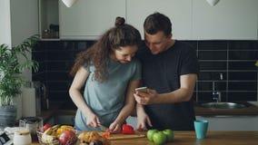 Die gelockte Frau, die nahe der Tabelle zu Hause schneidet roten Pfeffer in der Küche, ihr Ehemann tanzt, kommt, die Schale halte stock video footage