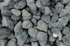 Die Gesamtheit von sehr großen groben grauen Steinen, zerquetscht an einer Steingrube, bestreuen Muster mit Kies stockfotos