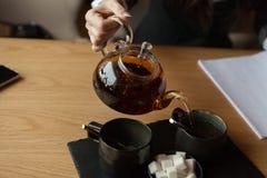 die Geschäftsdame gibt schwarz etwas Tee stockfoto