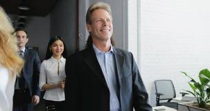Die Geschäftsfrau, die beim Telefonanruf spricht, beim Gehen mit ihren Geschäftsleuten team durch modernes kreatives Büro stock video