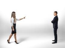 Die Geschäftsfrau, die Finger zeigt, unternimmt Schritt in Richtung auf Geschäftsmann Lizenzfreie Stockfotos