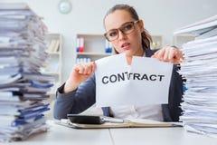 Die Geschäftsfrau, die ihren Vertrag auseinander reißt stockbild