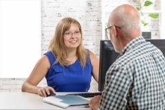 Die Geschäftsfrau, die Laptop verwendet und gibt, raten zu ihrem Kunden lizenzfreies stockbild