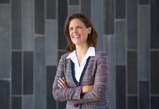 Die Geschäftsfrau, die mit den Armen lächelt, kreuzte gegen grauen Hintergrund Stockfoto