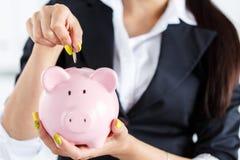 Die Geschäftsfrau, die Stiftgeld steckt, prägt in rosa piggybank Schlitz Lizenzfreie Stockbilder