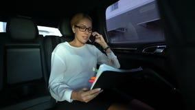 Die Geschäftsfrau, die durch den Bericht, fahrend in Auto schaut, entfernen Steuerung der Firma stock footage