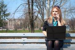 Die Geschäftsfrau mit Telefon und einem Notizbuch Lizenzfreie Stockbilder