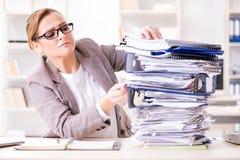Die Geschäftsfrau sehr beschäftigt mit laufender Schreibarbeit stockbilder