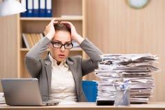 Die Geschäftsfrau unter Druck von zu vieler Arbeit im Büro lizenzfreie stockfotos