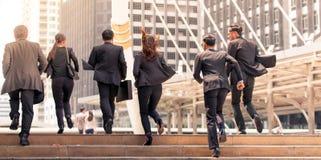 Die Geschäftsleute, die das Laufen in StadtHauptverkehrszeiten bewegen, winken zu Stockfoto