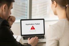 Die Geschäftsleute, die Laptopschirm mit Anwendung betrachten, fielen aus lizenzfreie stockbilder