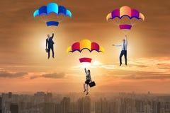 Die Geschäftsleute, die unten auf Fallschirme fallen Lizenzfreie Stockbilder