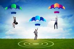 Die Geschäftsleute, die unten auf Fallschirme fallen Stockbild