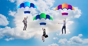 Die Geschäftsleute, die unten auf Fallschirme fallen Lizenzfreies Stockfoto